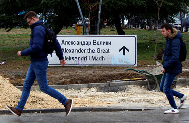 A boy runs past a sign for Alexander the Great Airport which was removed due to road construction in Skopje