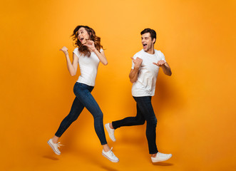 Photo of energetic beautiful couple running together along yellow backgroundand and pointing fingers backward on copyspace