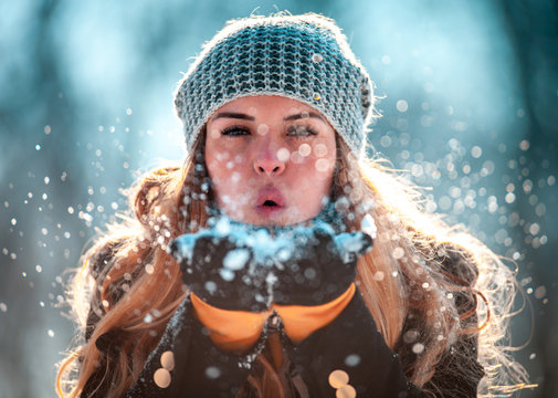 Winter woman blowing snow outdoor at sunny day, flying snowflakes