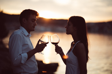 Two young people at the beach,making a toast for special occasion.Looking at the sun,enjoying the view with two glasses of wine.Drinking red wine.Celebration of anniversary.Birthday surprise.Honeymoon