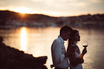 Two young people enjoying a glass of red wine in the sunset on the seaside.Healthy glass od homemade red wine,Mediterranean culture.Warm climates,seaside living couple.Seaside vacation experience