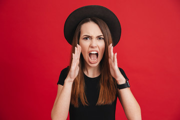 Portrait of an angry stylish girl wearing hat shouting