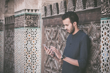 Young Muslim man using his mobile phone in casual clothing beside the wall with Moroccan decoration