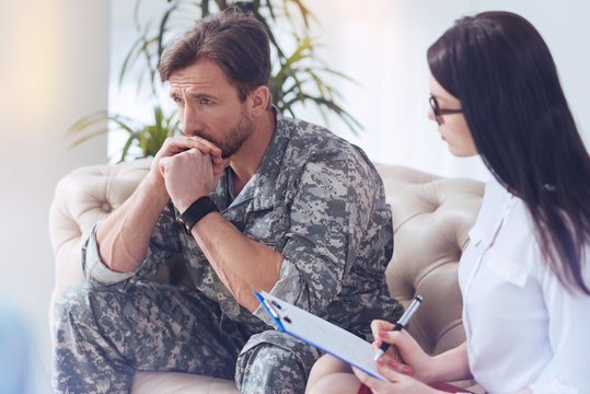 Getting through tough times. Experienced soldier sitting on a sofa and passing his military life in review while attending a female psychotherapist.