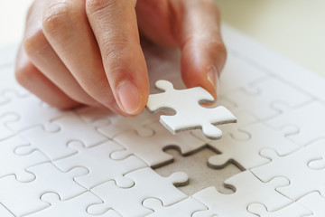 Woman's hand placing put the last white jigsaw puzzle piece to complete the mission, business success concept