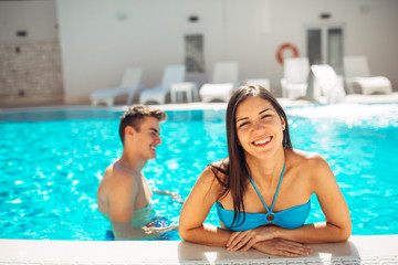 Smiling cheerful woman swimming in a clear pool on a sunny day.Having fun on vacation pool party.Friendly female enjoying relaxing resort vacation.Summertime relaxation,weekend fun.Body confidence