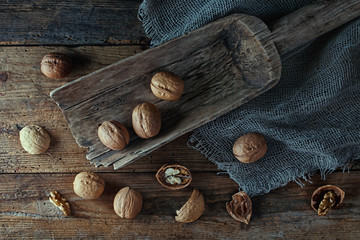 .Walnuts in a wooden scoop on an old village table. Low key.