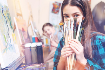 Creative studying. Pretty teenage girl hiding her face behind many painting brushes while sitting at a painting easel and smiling into the camera.