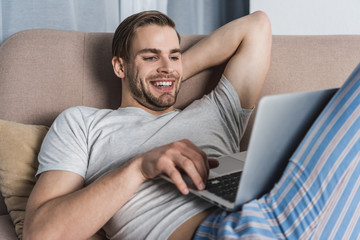 young smiling freelancer in pajamas working with laptop on couch