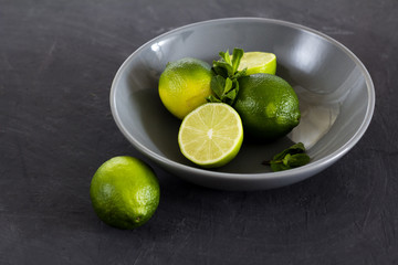 Limes and mint in a plate on a black background.