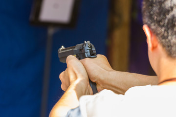 Blurred Image - Man practicing shooting in the amusement park. selective focus the gun