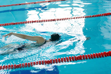 Young girl in goggles and cap swimming crawl stroke style in the blue water pool.