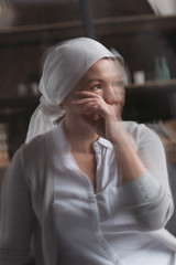 selective focus of sick mature woman in kerchief looking away