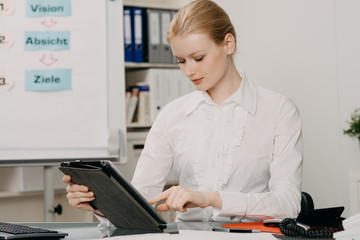 attractive young woman works on tablet in office