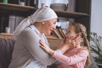 side view of sick grandmother and cute little granddaughter smiling each other