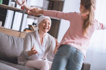 happy sick grandmother in kerchief looking at cute little granddaughter