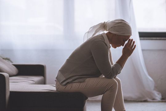 side view of upset sick mature woman in kerchief sitting at home, cancer concept