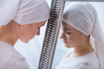 side view of young sick woman in kerchief leaning at mirror