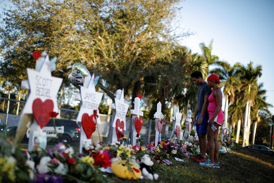 Adin Chistian, student of the Marjory Stoneman Douglas High School and his mother Denyse, look at the crosses and Stars of David placed in front of the fence of the school to commemorate the victims of the mass shooting, in Parkland