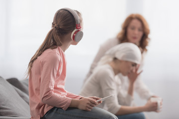 child in headphones using digital tablet and looking at sick mother and grandmother talking behind
