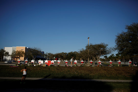 A woman touches one the Stars of David placed next to crosses in front of the fence of the Marjory Stoneman Douglas High School to commemorate the victims of the mass shooting, in Parkland