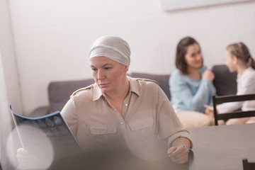sick mature woman in kerchief looking at mri scan