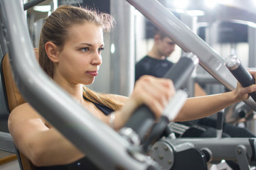 Close up portrait of sporty blonde girl workout on exercise machine in gym.