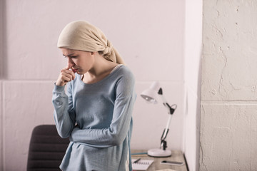 portrait of upset sick young woman in kerchief, cancer concept