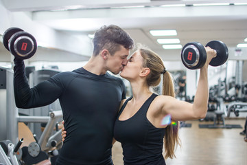 Beautiful young couple with weights kissing in the gym.