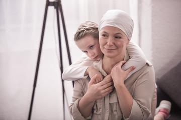 cute little child hugging sick grandmother in kerchief