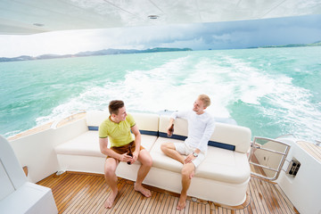 Friendship and vacation. Two young handsome men talking and drinking beer on the yacht sailing the sea.