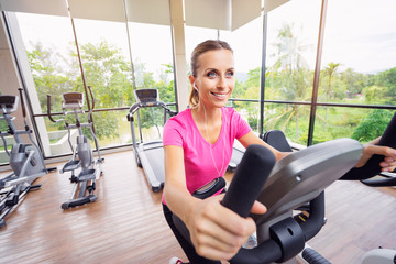 Healthy lifestyle and sport. Pretty young woman exercising in gym.