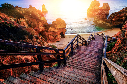 beautiful Atlantic ocean view horizon with sandy beach,  rocks and waves at sunrise. Algarve,  Portugal