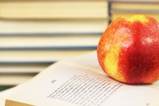 A large red apple on an open book with Shakespeare's sonnets on the background of a shelf with books