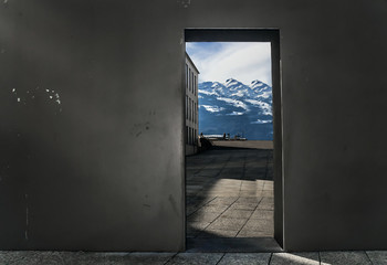 A beautiful pure scene of high snowy mountains and a clear blue sky visible through a doorway of a grey, dirty and grunge wall. The photo was shot on a street of Vaduz, Liechtenstein.