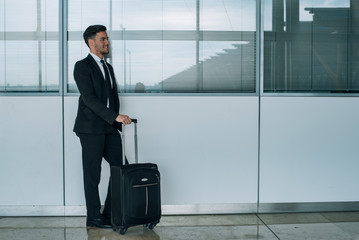 portrait of young  businessman smiling at the airport with suit