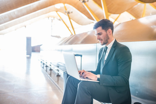 businessman working at the airport with laptop smiling waiting for his flight with luggage