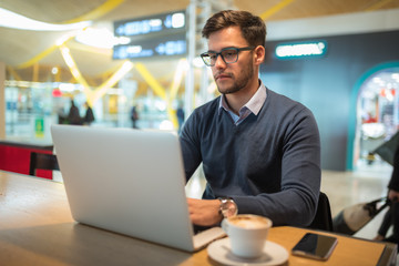 young man at the airport working with laptop using his mobile phone and drinking coffee waiting for his flight