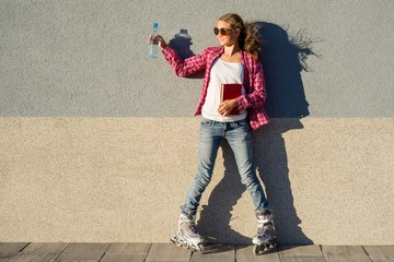 Girl teenager for an active lifestyle. Poses on the background of the wall is shod in the quad roller skates, holds a book and a bottle of water