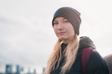 urban portrait of teen girl walking in the city in autumn or spring