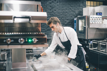 Cook on restaurant kitchen with smoke