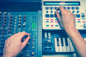 male DJ or sound engineer hands playing digital music on professional studio equipment