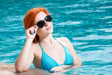 Portrait of a beautiful woman getting out of a swimming pool. beautiful long hair tanned model posing by blue pool water. Outdoor summer portrait of sexy girl in sunglasses. woman in red swimsuit.