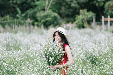 Portrait young woman in red dress smelling white cutter flower in garden.