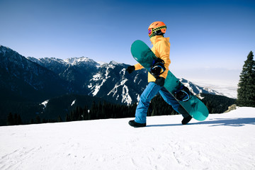 one snowboarder with snowboard walking on winter mountain top