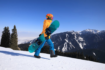 one snowboarder with snowboard walking on winter mountain peak