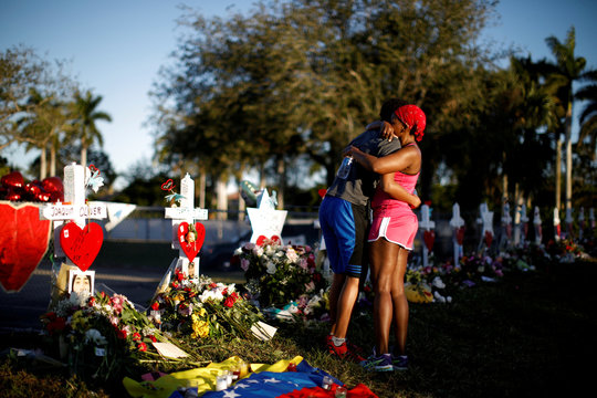 Adin Chistian, student of the Marjory Stoneman Douglas High School, embraces his mother Denyse, next to the crosses and Stars of David placed in front of the fence of the school to commemorate the victims of a shooting, in Parkland