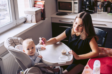 Mom with a small child in the kitchen. Feeds the newborn from the spoon.
