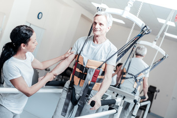 Learning to walk. Vigorous old grey-haired man smiling and exercising on a training device and learning to walk and a young dark-haired female trainer standing near him and touching his hand