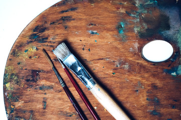 Real art wooden palette with blobs of paint and a brush on white background. Concept Art and Craft